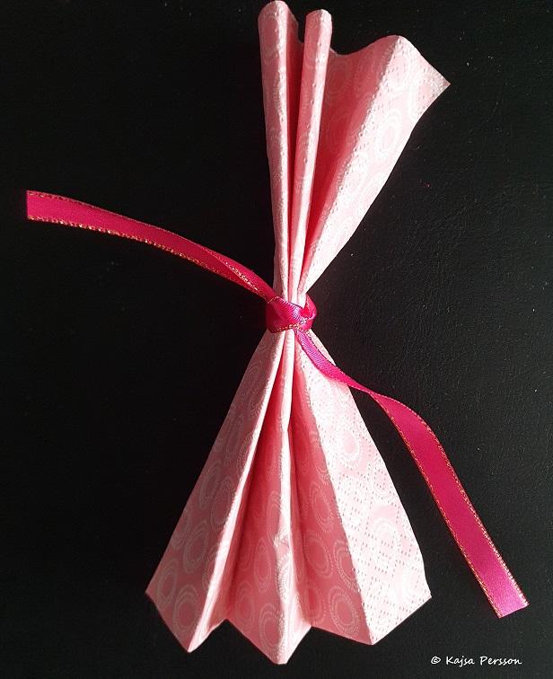 Knyt en rosett mitt på servetten med ett fint sidenband