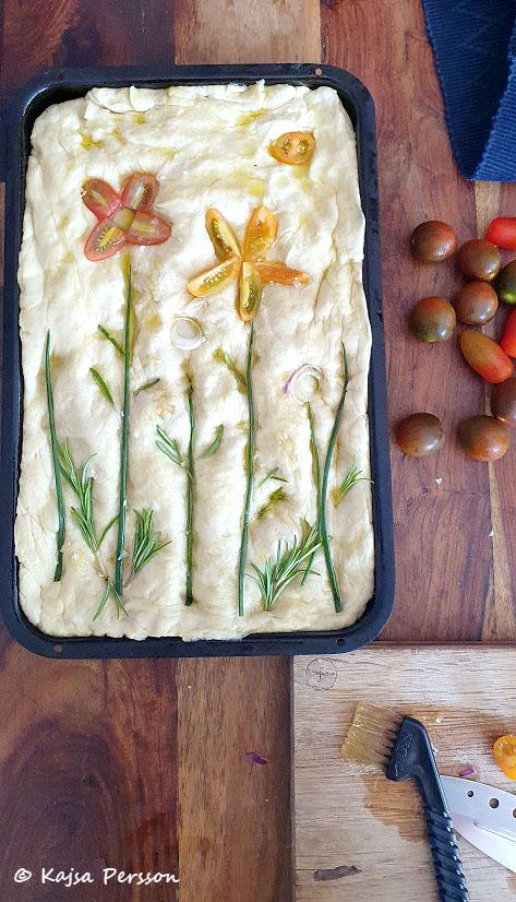 Sätter fast tomater, gräslök, rosmarin och rödlök för att ge foccacian ett snyggt mönster