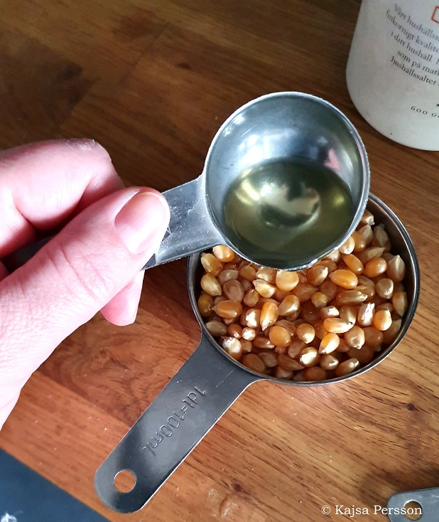 En matsked rapsolja hälls över en deciliter popcorn