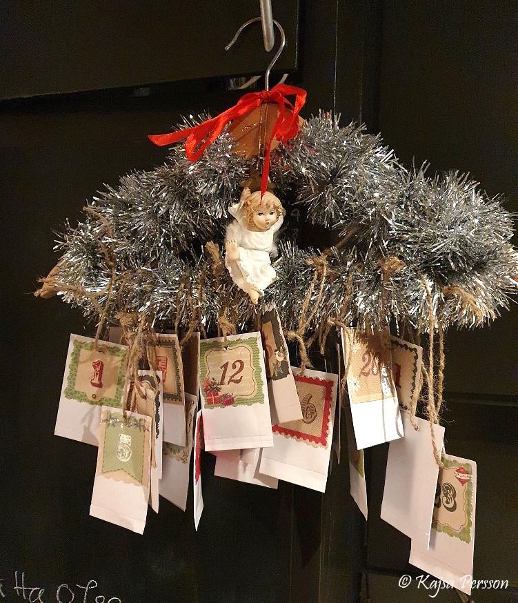 Hemmagjord adventskalender på en galge med glitter och en hängande ängel