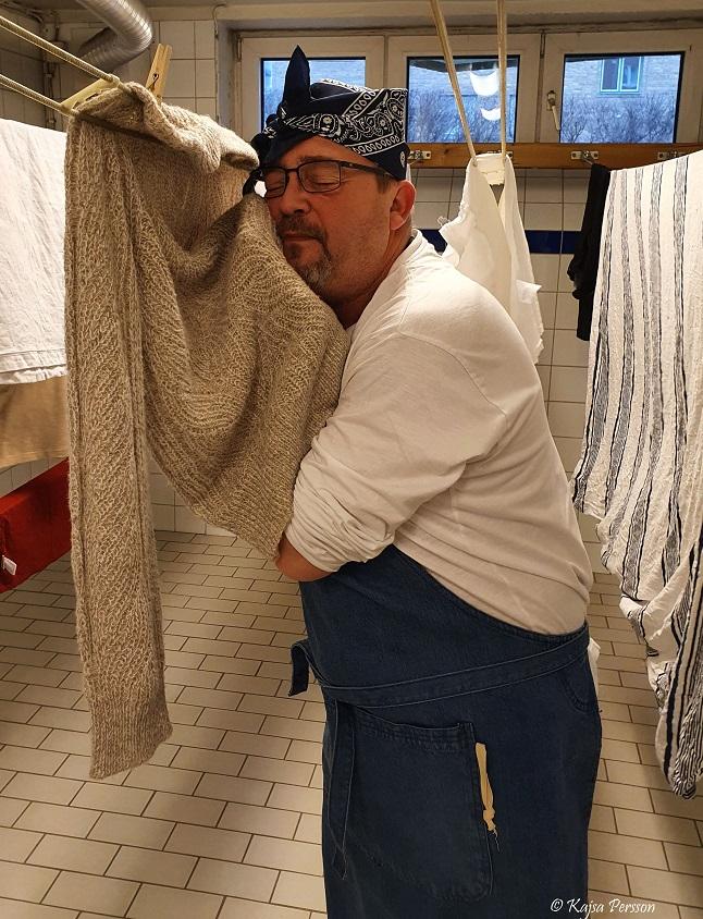 Mannen gosar med tvätten i torkrummet