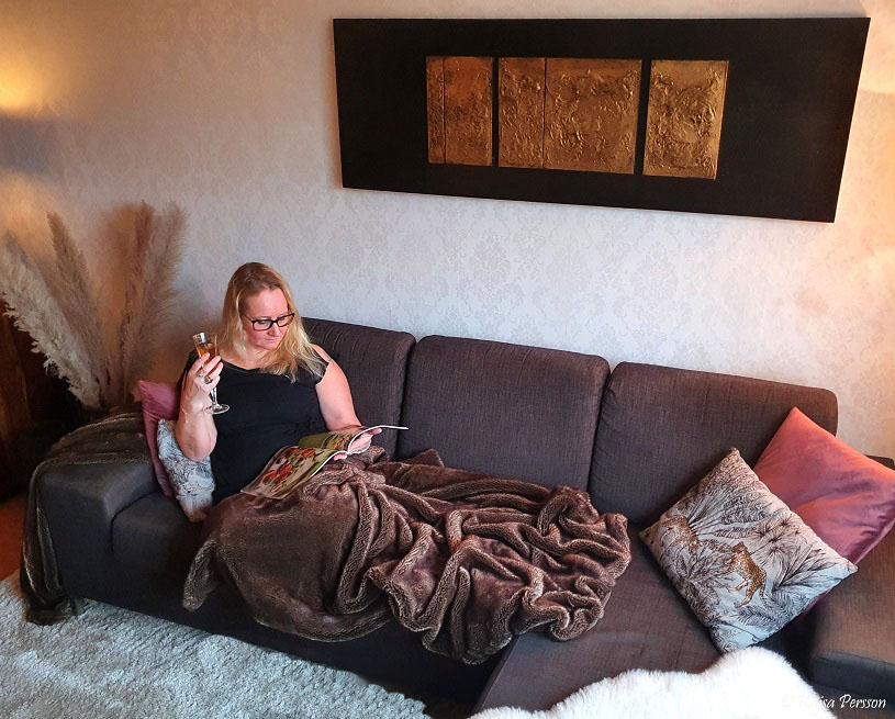 Kvinna i soffan som läser tidning och dricker champagne