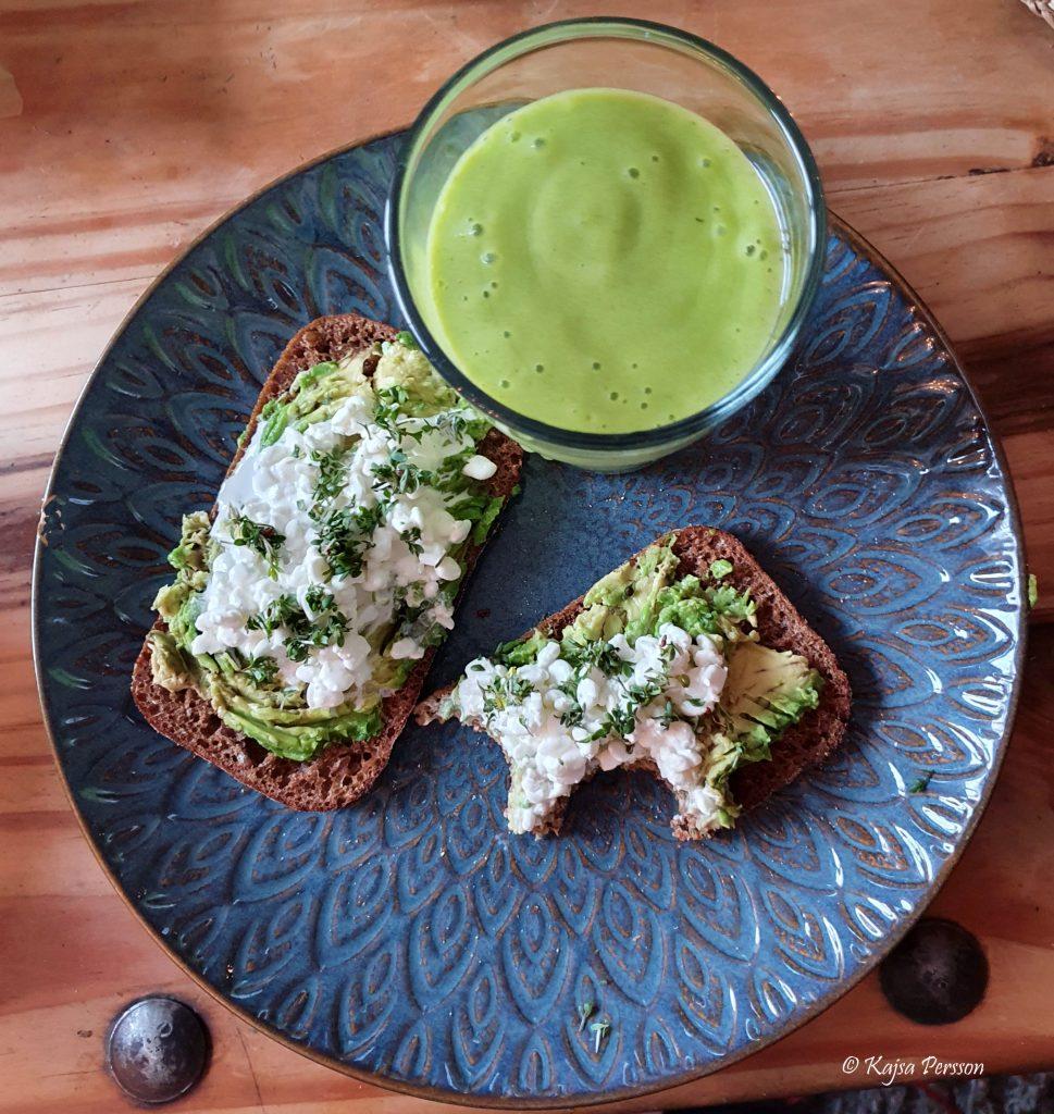 Grön mango smoothie och en avokado keso smörgås på en blå tallrik till Oxen