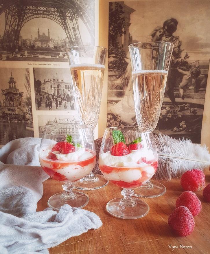 Dessert i ett glas med apelsinmarinerade jordgubbar med fluffig grädde