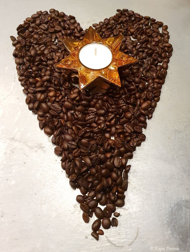 Kaffe bönor som bildar ett hjärta med ett guldrigt stjärnljus