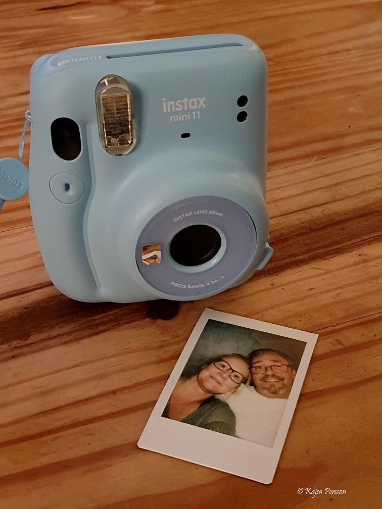 Ljusblå polaroidkamera med ett foto på ett bord