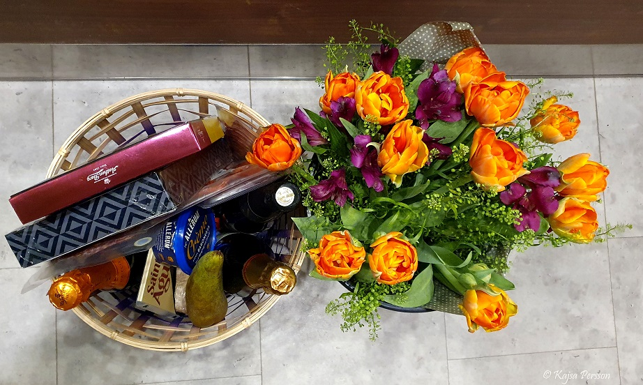 Avskedsgåvor med delikatesskorg och orangea blommor