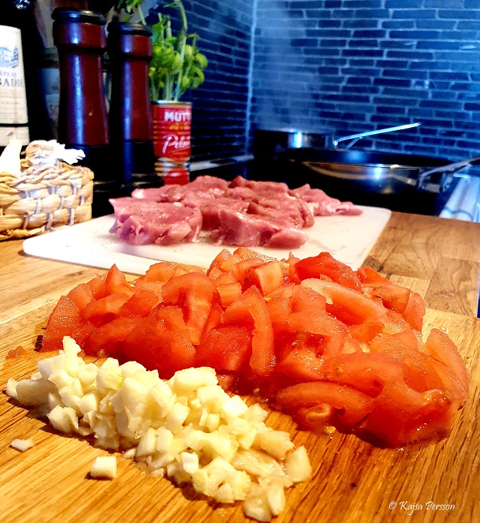 Goda ingredienser med vitlök, tomat, basilika och fläskfile till fredagsmiddag