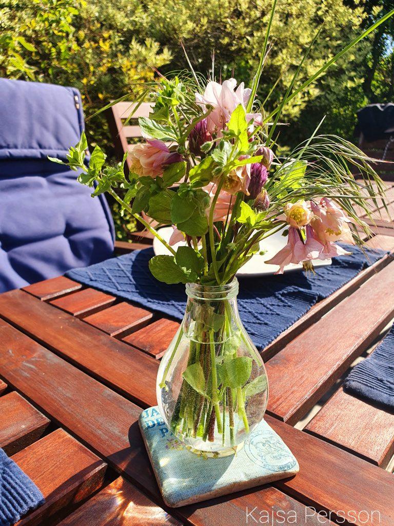 Sommarblommor i glasvas i solen