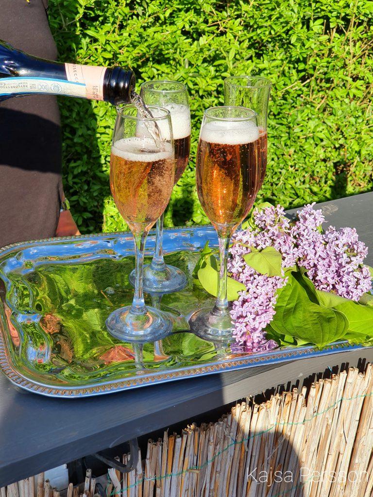 Fyra Champagneglas där man häller upp rosé champagne. silverbricka med syrenblommor