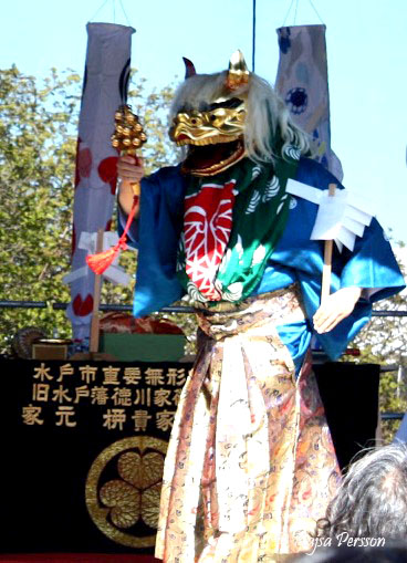 En person med guldmask och japanska kläder