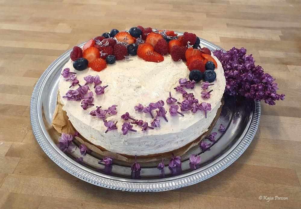 Jordgubbscheesecake dekorerad med färska bär, kanderade syrener och färska syrenblommor