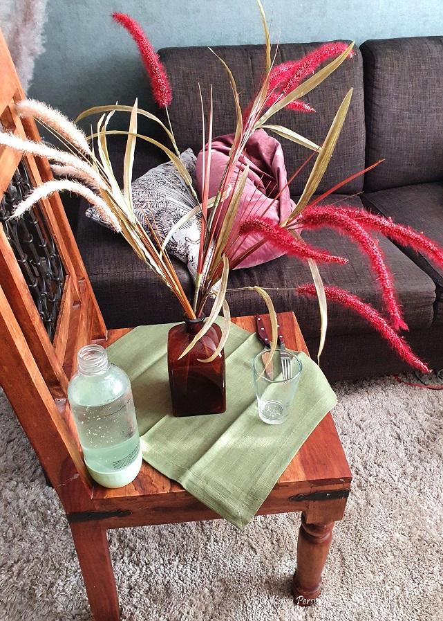 Stol som bord, dukat för middag på skämt med en stor vas med torkade blommor mitt på