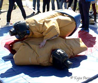 Lekfullt med sumobrottare i sumodräkter på en blå matta utomhus