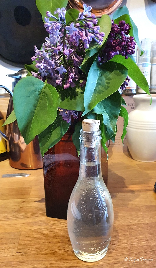 Syren syrup i en fin glasflaska med en bukett syrener i en brun glasflaska bakom