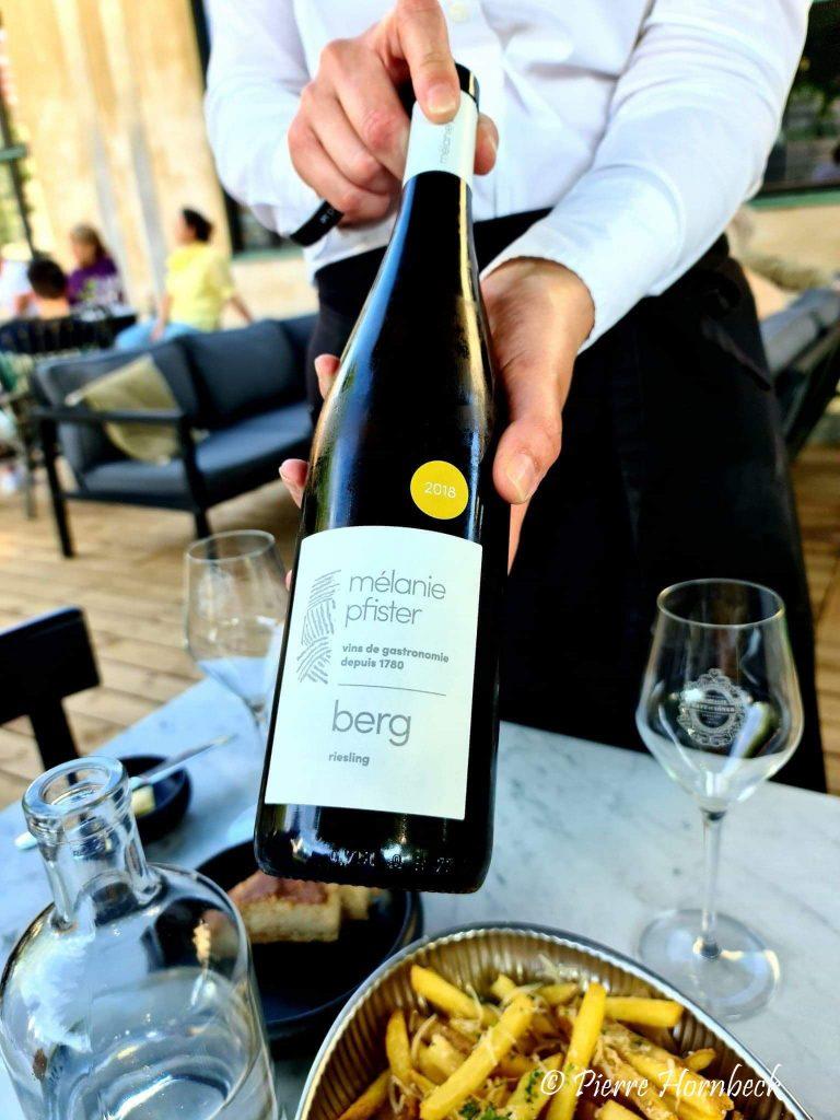 En person håller en flaska vin Melanie Pfister Riesling berg rån Alsace Restaurang Ivar i Malmö