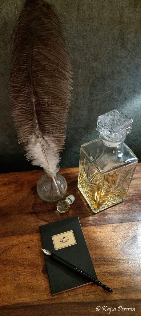 Anteckningsbok, fjäder och en karaff med Whiskey på en brun bänk