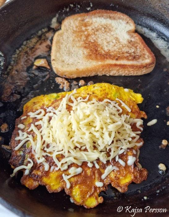 Stekt macka och en stekt omelett med ost i ett stekjärn