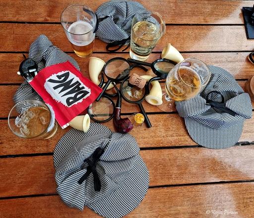 Detektivhattar, förstoringsglas, öl, bang, pipor på ett bord