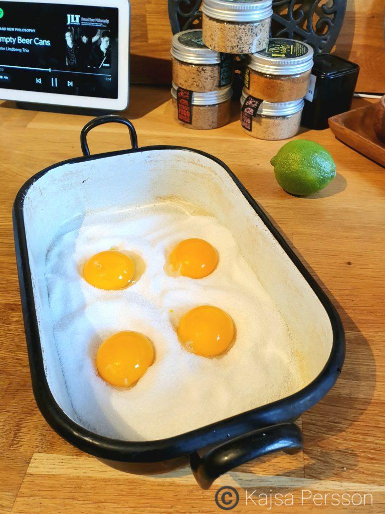 Fyra Äggulor på salt och sockerbädd i en svart ugnsform, ska bli garvade äggulor