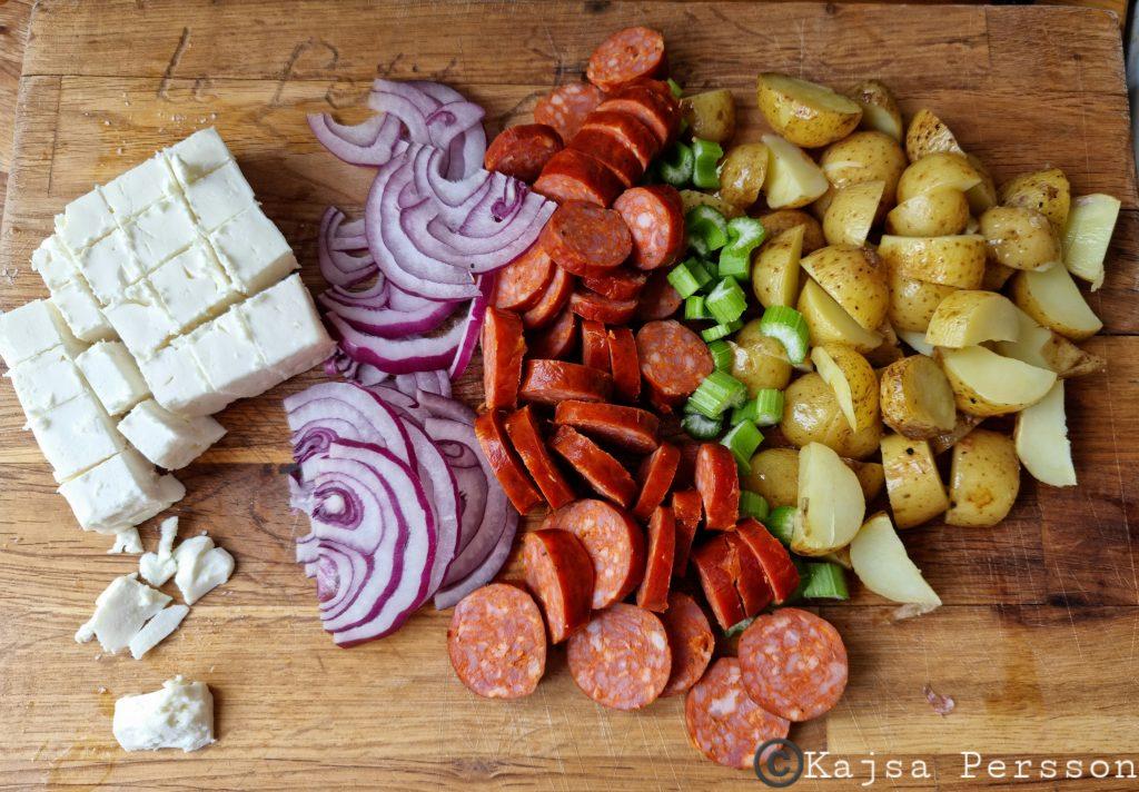Potatis, korv, selleri och fetaost på skärbräda