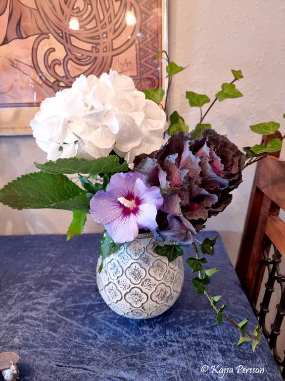 Blombukett i vit vas med kål, murgröna, vit hortensia och lila hibiskus