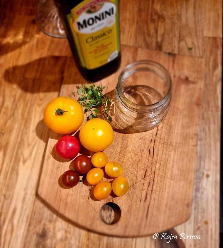 Tomter, timjan, glasbur och olja på en skärbräda är ett av de tomat recept jag testar