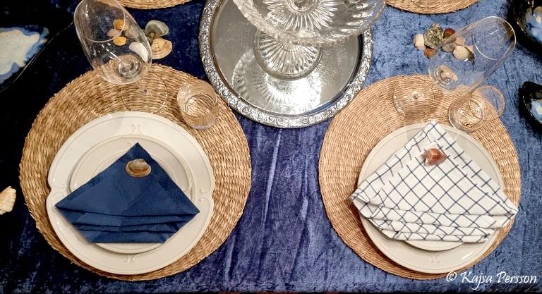Servettvikning med blå pappers servett och en rutig tygservett i vitt och blått med snäcka på