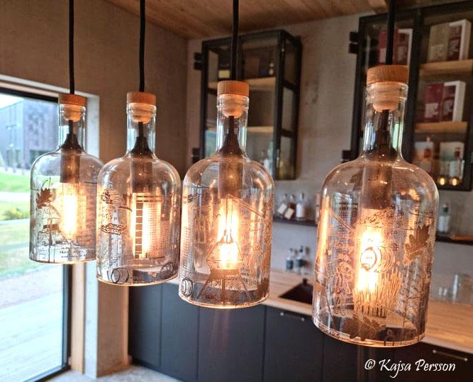 Fyra Mackmyra flaskor som hängande lampor