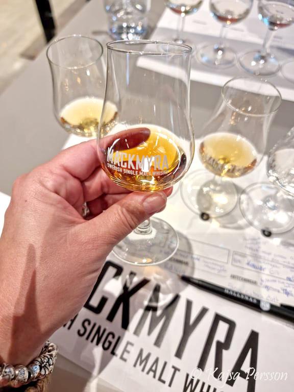 Ett glas Mackmyra i en hand på whiskeyprovning