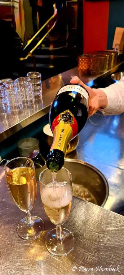 Två champagne glas och en hand som häller Bollinger flaska