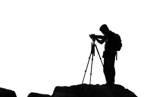 Sort/hvid grafisk gengivelse af landskabsfotograf der er ved at sætte sit kamera på et stativ.