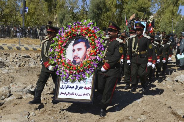 An honor guard carries a photo of Gen. Abdul Raziq, the Kandahar police chief killed in October.