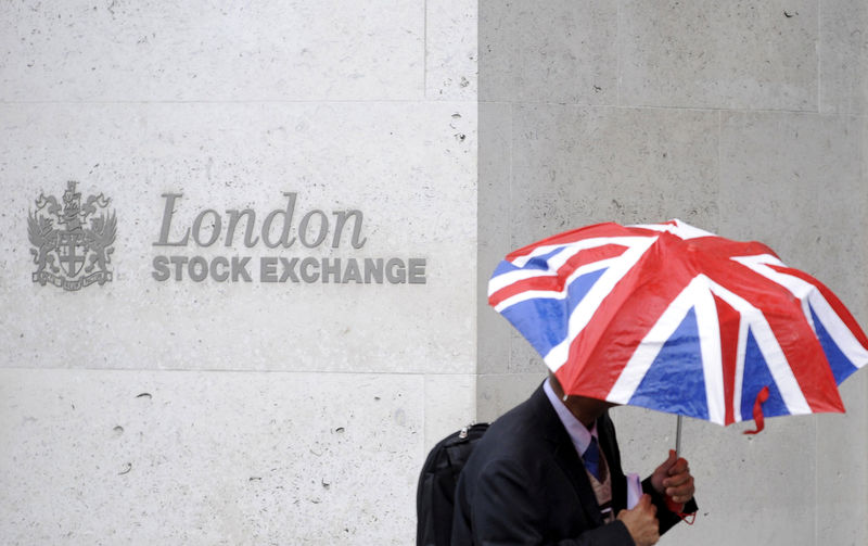 © Reuters. A worker shelters from the rain as he passes the London Stock Exchange in London