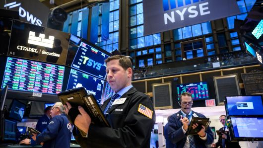 Traders and financial professionals work ahead of the closing bell on the floor of the New York Stock Exchange (NYSE)