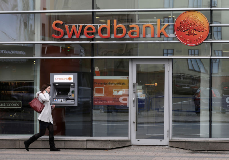 © Reuters. FILE PHOTO: A woman walks past Swedbank  branch in Riga