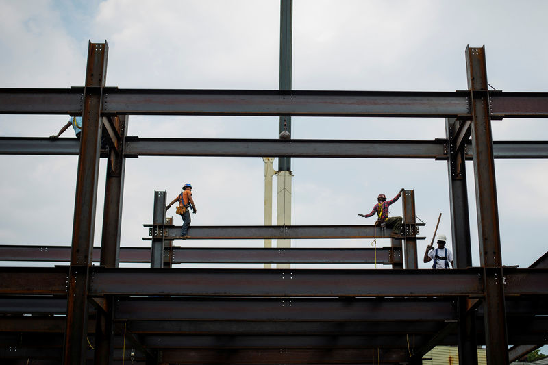 © Reuters. FILE PHOTO: Iron workers install steel beams during a hot summer day in New York