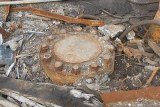 A round lid welded shut among debris
