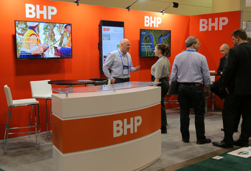© Reuters. Visitors to the BHP booth speak with representatives during the PDAC convention in Toronto