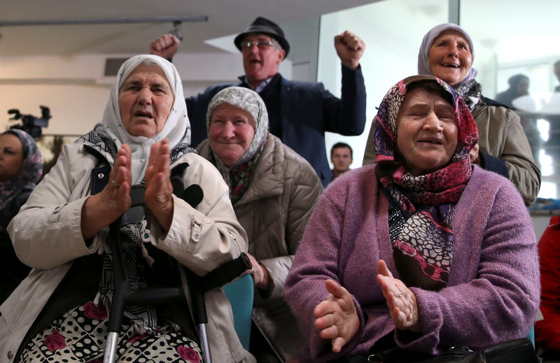 © Reuters. People react after the verdict on former Bosnian Serb political leader Radovan Karadzic's appeal of his 40 year sentence for war crimes, in the Memorial centre Potocari near Srebrenica