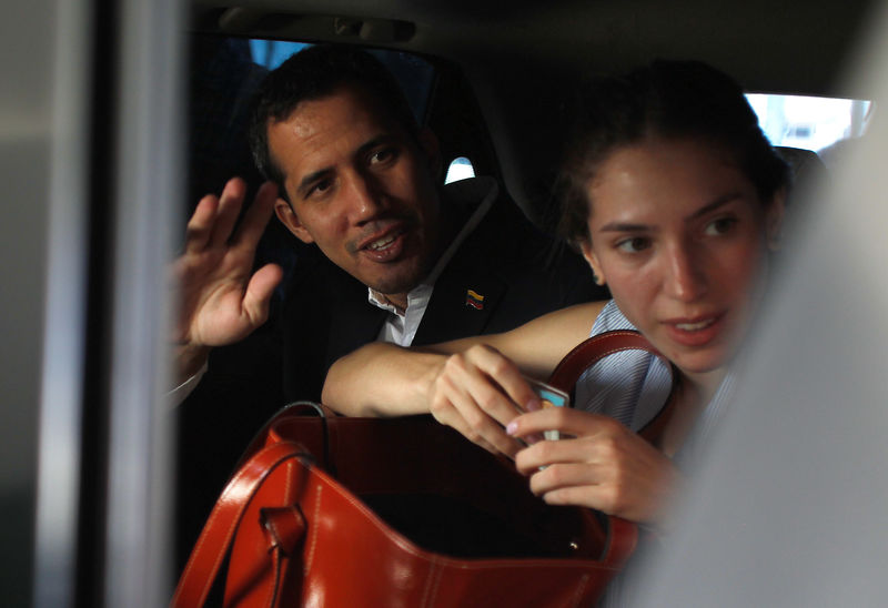© Reuters. Venezuelan opposition leader Juan Guaido, who many nations have recognized as the country's rightful interim ruler, waves next to his wife Fabiana Rosales while leaving a hotel in Salinas