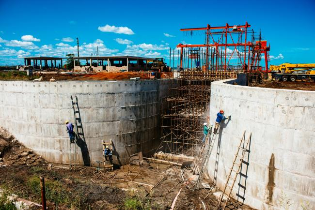 © Bloomberg. Workers build a hydro pumping station which will supply water from the Limpopo river to nearby rice farms owned by Wanbao Grains & Oils Co., a Chinese company, in the Limpopo Valley near Xai Xai village, Mozambique, on Friday, March 24, 2017. The granaries and surveillance cameras in this corner.