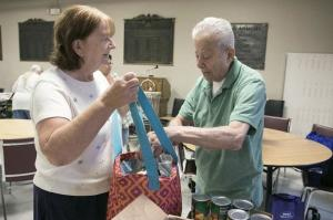 Christine Grenier gets help with some canned food from Fitchburg Senior Center volunteer Paul Thonis during a recent program. The Senior Center is hoping