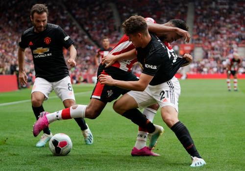 Soton's Sofiane Boufal tussles with United's Daniel James (right) as Juan Mata looks on.