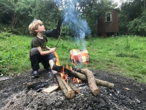 Young boy next to wood fire in a field