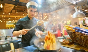 Man in a chef's hat tossing food in a wok at Marketplace restaurant.