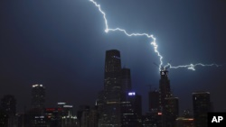 Lightning strikes a skyscraper in Central Business District during a rainstorm in Beijing, Wednesday, Sept. 7, 2016. (AP Photo/Andy Wong)