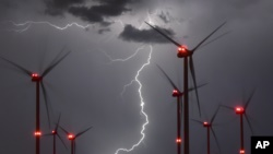 In this Aug. 1, 2017 photo lightning illuminate the night sky over the Odervorland wind farm in the Oder-Spree district near to Sieversdorf, Germany. (Patrick Pleul/dpa via AP)