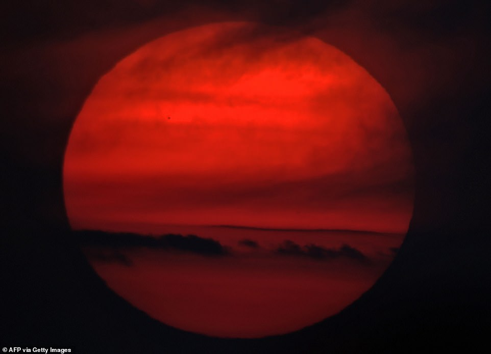 A photographer in Kuwait captured this photograph of Mercury passing in front of a deep red sun today. The planet is the closest to our Sun and can be seen as a tiny black dot between the 10 and 11 o'clock positions of the star