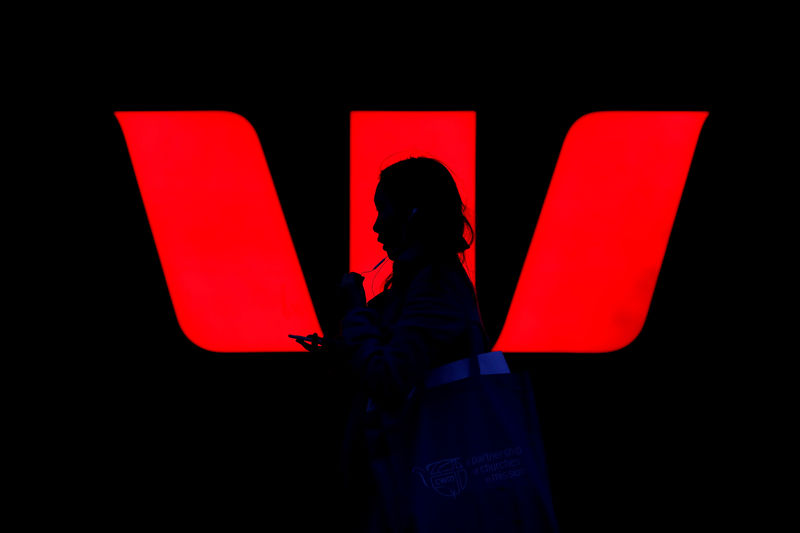 © Reuters. FILE PHOTO: A woman walks past an illuminated logo for Australia's Westpac Bank in Sydney
